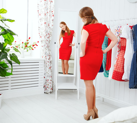 young woman in a red dress looks in the mirror and choose clothes Фото со стока