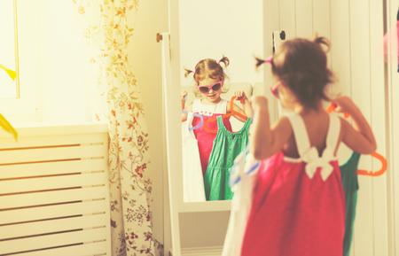 Dziewczynka dziecko patrzy w lustro i wybrać sukienki