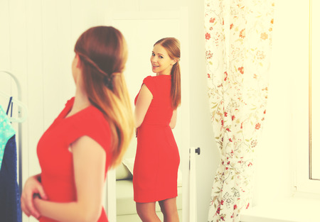 young woman in a red dress looks in the mirror Фото со стока