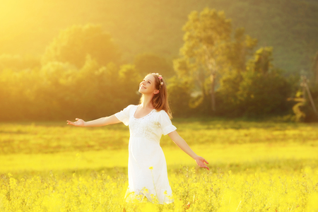 Happy woman enjoying the summer outdoors in the meadow of yellow flowers