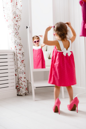 little girl child fashionista looking in the mirror at home in a pink dress, shoes and sunglasses