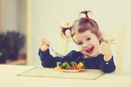 eating up: happy child girl loves to eat vegetables and showing thumbs up Stock Photo