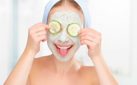 肌の顔と目のキュウリのマスクを持つ面白い少女