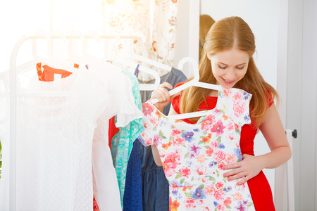 young woman in a red dress looks in the mirror and choose clothes Stockfoto
