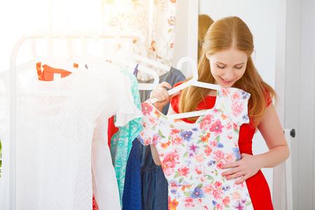 mujer joven en un vestido rojo se mira en el espejo y elegir la ropa