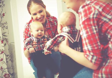 엄마와 아기가 거울을보고 집에서 미소를 짓는다. 스톡 콘텐츠