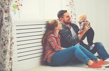 家庭: 幸福的家庭的母親和父親在家裡寶寶玩