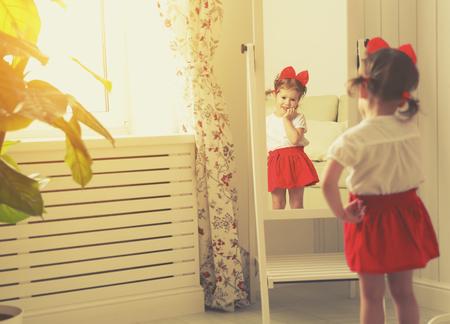 Dziewczynka dziecko fashionistka, patrząc w lustro w domu w czerwonej spódnicy, buty matki