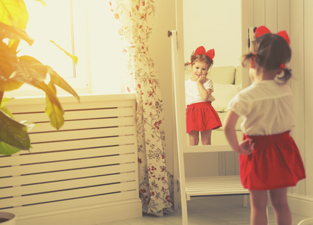 little girl child fashionista looking in the mirror at home in a red skirt, shoes of mother Stock Photo - 51917441