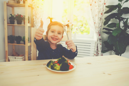 happy child girl loves to eat vegetables and showing thumbs up Stock Photo