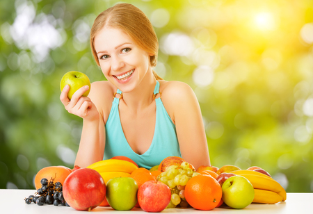 summer fruit: healthy vegetarian food. happy woman eating apple and fruit  in the summer