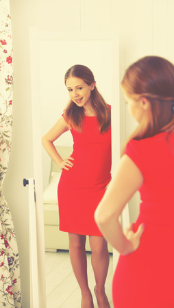 woman mirror: young woman in a red dress looks in the mirror Stock Photo