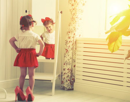 red heels: little girl child fashionista looking in the mirror at home in a red skirt, shoes of mother