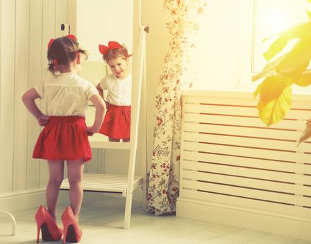 tacones rojos: pequeña fashionista niña niño que mira en el espejo en su casa en una falda roja, zapatos de la madre