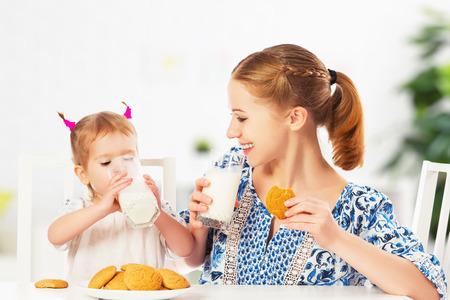 tomando leche: feliz madre de familia y su hija bebé niña niño en el desayuno: galletas con leche