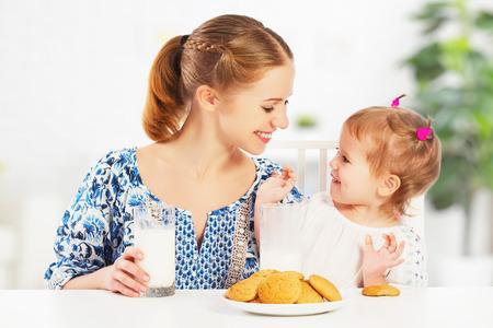 niños comiendo: feliz madre de familia y su hija bebé niña niño en el desayuno: galletas con leche