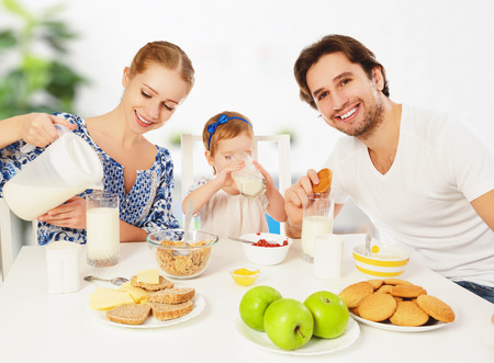 tomando leche: Feliz madre de familia, padre, hija bebé niño que desayunan en casa