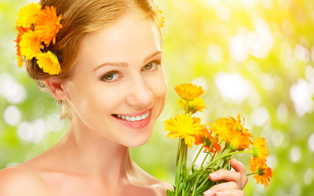 women hair: Beauty face of the young beautiful woman with orange yellow flowers in her hair