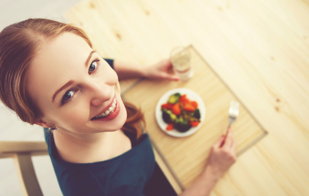 young healthy woman eats vegetables at home in the kitchen summer