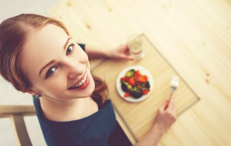 젊은 건강한 여자는 부엌 여름 집에서 야채를 먹는다.