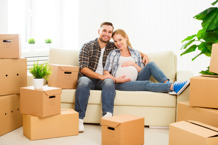 pregnant woman with husband: moving to a new apartment. young family pregnant wife and husband with cardboard boxes