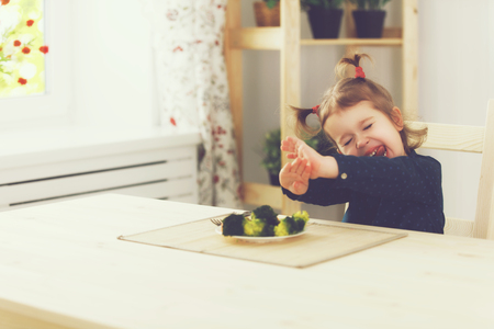 sad cute baby: child girl does not like and does not want to eat vegetables