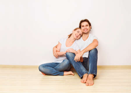 happy couple at home: Concept: The housing and mortgage for young families. couple on empty wall Stock Photo