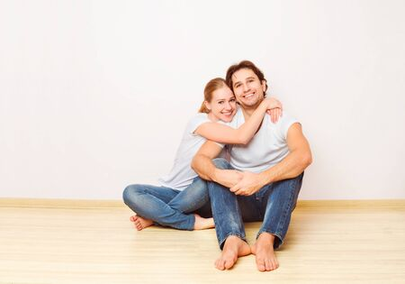 happy couple: Concept: The housing and mortgage for young families. couple on empty wall Stock Photo