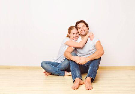 familias jovenes: Concepto: La vivienda y la hipoteca para las familias jóvenes. pareja en pared vacía
