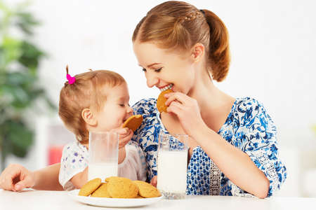 feliz madre de familia y su hija bebé niña niño en el desayuno: galletas con leche