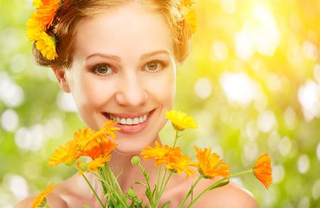 Schoonheid gezicht van de jonge mooie vrouw met oranje gele bloemen in het haar