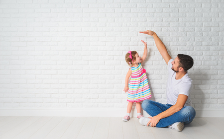 concept. Dad measures the growth of her child daughter at a blank brick wall 版權商用圖片