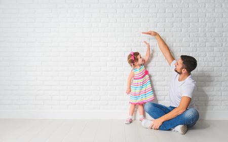 concepto. Papá mide el crecimiento de su hija hijo en una pared de ladrillos en blanco