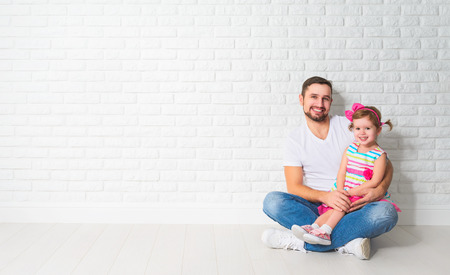concept of mortgage housing problems. Family father child daughter at a blank white brick wall