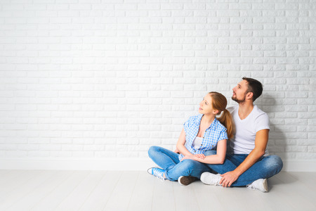 housing problems: concept of mortgage housing problems. Family couple at empty blank white brick wall