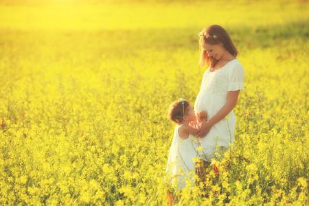 campo de flores: familia feliz, madre e hija niña niña embarazada en el prado de verano con flores amarillas