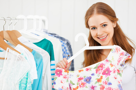 woman clothes: young woman chooses clothes in her wardrobe