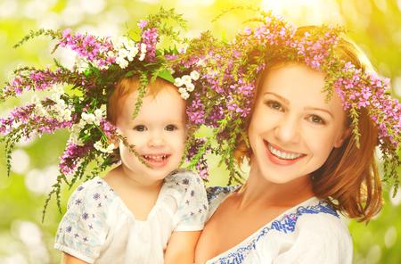 glücklich lachende Familie, die Tochter umarmt Mutter in Kränze aus Sommerblumen in der Natur