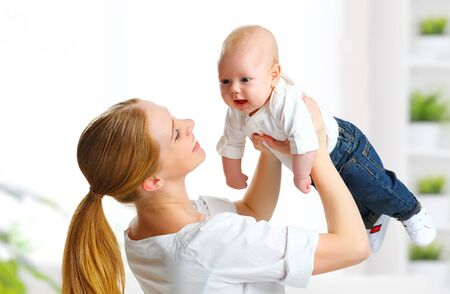 happy love: happy family playing mother  throws up child baby at home