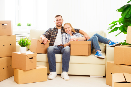 family moving house: moving to a new apartment. Happy family couple and a lot of cardboard boxes.