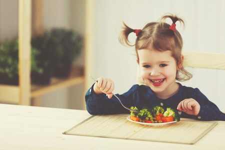 broccoli salad: the happy child girl  eating vegetables and laughs