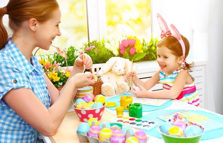 huevos de pascua: madre de familia feliz y chica niño pinta los huevos de Pascua en el hogar