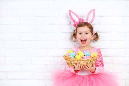 Happy child girl in a costume Easter bunny rabbit with ears and a basket of eggs Stok Fotoğraf