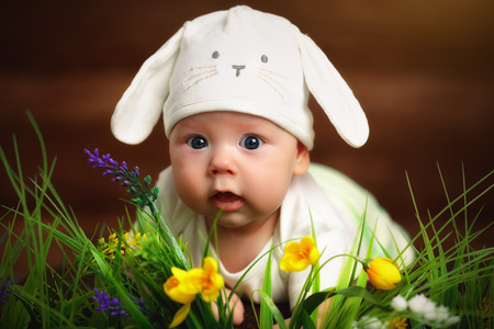happy child baby dressed as the Easter bunny rabbit lying on the grass on the lawn with flowers 스톡 콘텐츠