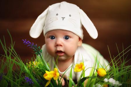 bebé feliz niño vestido como el conejo de Pascua conejo acostado en la hierba en el césped con flores Foto de archivo