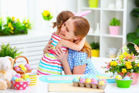 parents with baby: happy family celebrating Easter. mother and daughter hugging at home with decorations multi colored eggs and flowers