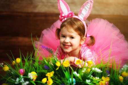 medow: Happy child girl in a costume Easter bunny rabbit with  eggs, grass and flowers
