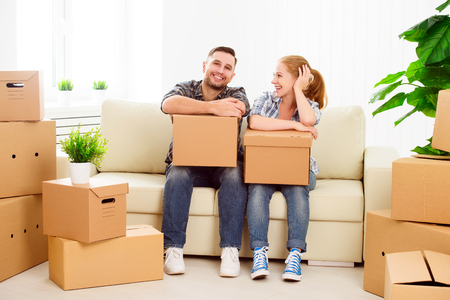 people moving: moving to a new apartment. Happy family couple and a lot of cardboard boxes.