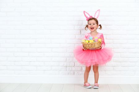 Niña feliz en un traje del conejo de conejito de Pascua con orejas y una cesta de huevos