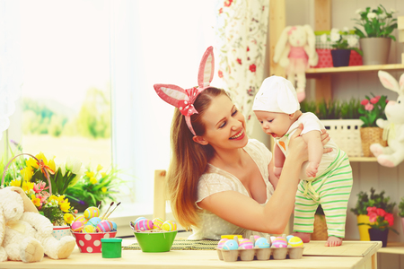 decorate: happy family celebrating easter mother and baby bunny ears at home with colorful eggs and flowers